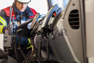 Feuerwehrmann mit Funkgeraete im Einsatzfahrzeug