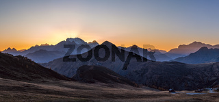 Sun glow in evening hazy sky. Mountain panoramic peaceful view from Giau Pass.