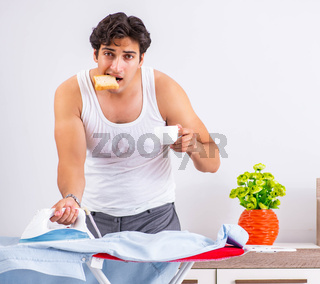 Young man ironing in the bedroom