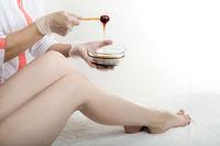 Shugaring master removes hair on her legs