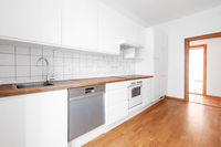 empty,  white kitchen or kitchenette with parquetfloor and wooden tabletop