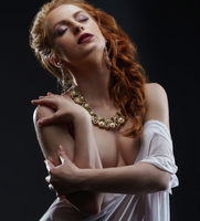 Sensuality and luxury. Red-haired model posing