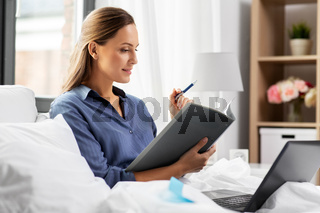 young woman with laptop and papers in bed at home