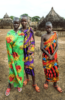 TOPOSA TRIBE, SOUTH SUDAN - MARCH 12, 2020: Teenagers wrapped in colorful bright fabric looking at camera against straw huts in village of Toposa Tribe in South Sudan, Africa
