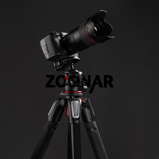 Professional photography equipment, digital mirrorless camera on tripod with dark gray background