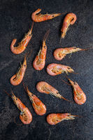 Boiled tiger prawns on black table. Tasty shrimps.