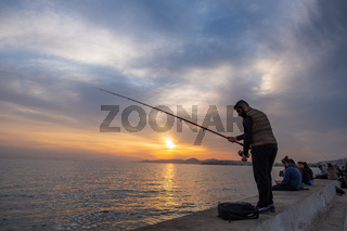 Beautiful sunset scene of a fisherman and other people enjoying themselves at the seafront in Palaio Faliro in Athens, Greece