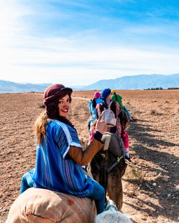 A beautiful Arab girl riding a camel in Morocco during a travel
