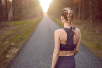 Sporty young woman walking at sunrise