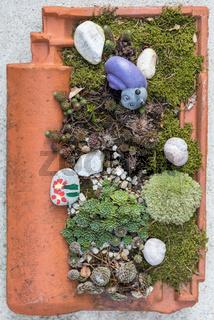 Gartendekoration mit Dachziegel aus Ton bepflanzt und gestaltet