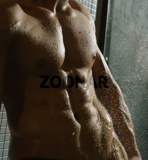 Nude man taking shower studio portrait