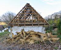 Alter hölzerner Dachstuhl ohne Eindeckung auf einem Weinhauerhaus und Bündel von Stroh für die neue Eindeckung