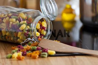 Glas mit Pastanudeln liegend mit Kochlöffel