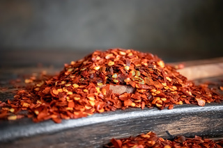 Flakes of red hot chili pepper in wooden spoon closeup on a kitchen table.