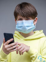 Boy with face mask and smartphone
