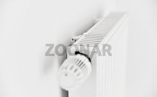 Heizung mit Plattenheizkörper und Thermostat an Wand