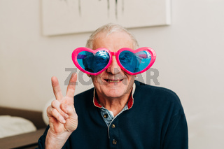 Happy elderly man portrait with heart shaped glasses at home, love concept