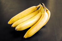 Bunch of bananas on a black wooden table