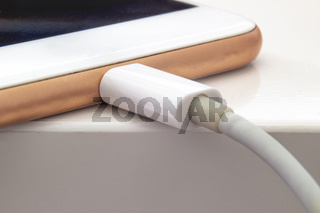 Close up of a smart phone changing on a white table