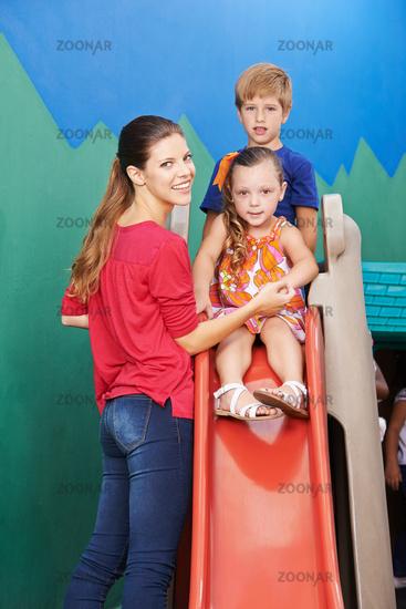 Frau neben Kindern auf Rutsche im Kindergarten