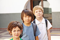 Drei Kinder stehen auf dem Schulhof