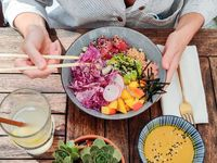 Woman eating tasty colorful healthy natural organic vegetarian Hawaiian poke bowl using asian chopsticks on rustic wooden table. Healthy natural organic eating concept