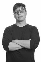 Portrait of nerd man wearing eyeglasses with arms crossed in black and white