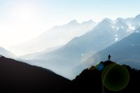 Spectacular mountain ranges silhouettes. Man reaching summit enjoying freedom. View from Top of Mount Corno di Tres, Tresner Horn. Trentino, South Tyrol, Alps, Italy.