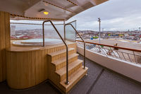 Outdoor jacuzzi whirlpool on the deck of a Norwegian cruise ship lying in port in Trondheim with city in background