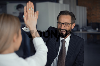 Happy Successful Businessman giving high five with businesswoman standing back in foreground. Teamwork concept