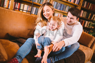 Christmas family portrait. Young Caucasian family in identical clothes having fun on sofa in living room with large library of books and Christmas tree in evening. Happy New Year and Merry Christmas