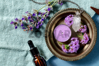 Essential oil and its uses concept with copy space. Aromatic candle and a vial for perfume lavender and vervain, shot from above