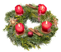 Top view of a decorated Christmas wreath made of fir branches with burning red candles isolated on w