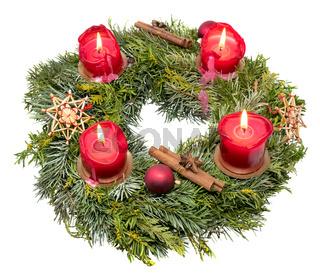 Blick von oben auf einen Verzierter Adventskranz aus Tannenzweigen mit brennenden roten Kerzen