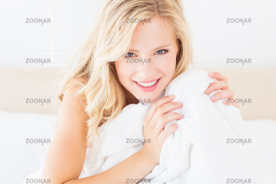 Pretty young blonde covering herself with duvet