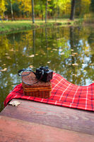 The old camera lies on a suitcase on a red plaid blanket. Wooden bridge near the lake.