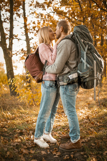 Couple of tourists in love in the autumn forest. Young man and woman kisses and hugs while standing against the backdrop of colorful autumn nature backlit by sunlight. Full-length portrait