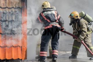 Firefighters extinguishing fire from fire hose, using firefighting water-foam barrel with air-mechanical foam