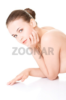 Attractive naked woman proping her head while lying on the floor.