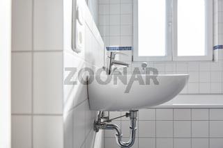 Waschbecken mit Wasserhahn im hellen weißen Bad