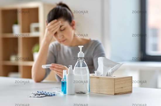 medicines and sick woman with thermometer at home