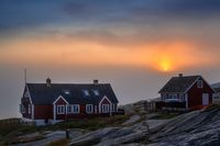 Greenlandic red houses on the coast with the setting sun