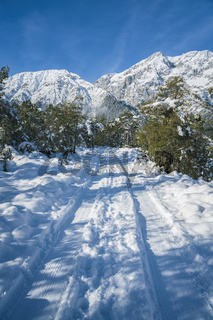 Winter walking path through snow in Austrian Alps at Mieming, Tyrol, Austria