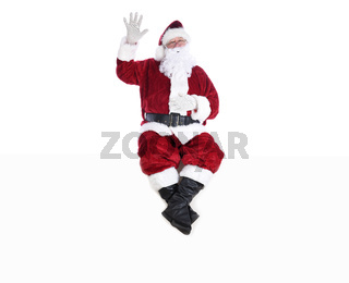 Senior man in traditional Santa Claus Suit sitting on a white wall with one hand in the air and the other on his belly and his eyes closed.