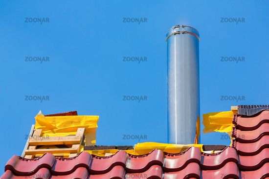 New roof with roof tiles and metal chimney pipe