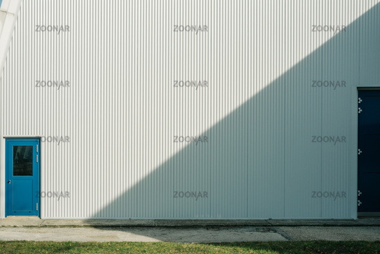 Blue doors and industrial background with empty copy space. Wall divided through light and shadow. Abstract business concept.