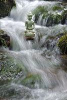 buddha sculpture is sitting in water cascade