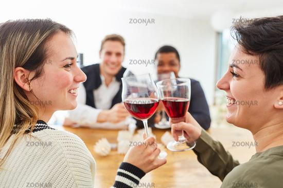 Glückliche Freunde prosten sich zu mit Glas Wein zu Hause