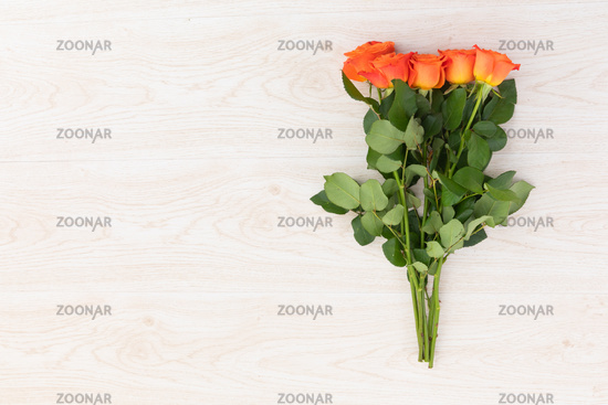 Bunch of orange roses lying on wooden background