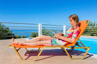 European woman on lounger reading tablet